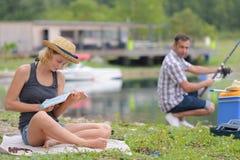 Книга чтения женщины пока рыбная ловля супруга стоковое изображение