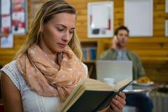 Книга чтения женщины пока человек говоря на телефоне в предпосылке Стоковые Изображения
