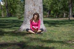 Книга чтения женщины сидя в траве рядом с деревом Стоковое Фото