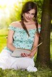 Книга чтения женщины сидя на траве в парке Стоковая Фотография