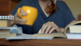 Книга чтения женщины таблицей и выпивать от оранжевой чашки сток-видео