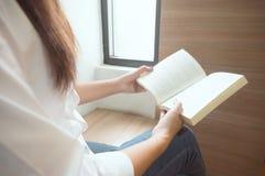 Книга чтения женщин и ослаблять в библиотеке Селективный фокус стоковое фото rf
