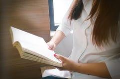 книга чтения женщин и ослаблять в ее живущей комнате Стоковые Изображения