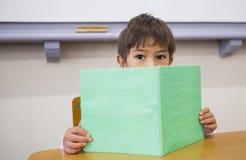 Книга чтения зрачка на столе Стоковая Фотография RF