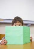 Книга чтения зрачка на столе Стоковые Изображения RF