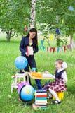 Книга чтения красивого азиатского учителя женщины говоря к shoolgirl Стоковое Фото