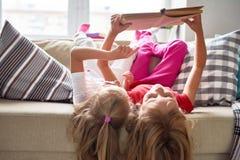 Книга чтения маленьких девочек дома Стоковая Фотография