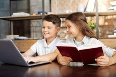 Книга чтения маленькой девочки пока ее брат играя на компьтер-книжке Стоковое Фото