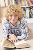 Книга чтения мальчика в спальне Стоковая Фотография RF
