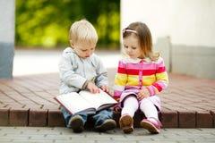 Книга чтения мальчика и девушки Стоковая Фотография RF