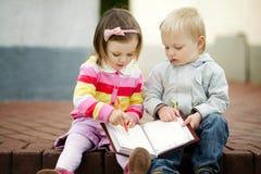 Книга чтения мальчика и девушки Стоковое Изображение