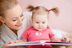 Книга чтения мамы и младенца внутри помещения стоковая фотография rf