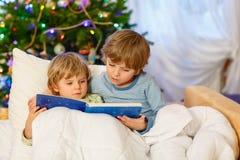 Книга чтения 2 маленькая мальчиков отпрыска на рождестве Стоковые Фото