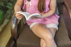 Книга чтения маленькой девочки на стуле Стоковые Изображения