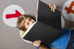 Книга чтения мальчика на поле дома стоковое изображение