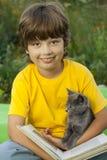 Книга чтения мальчика с котенком в дворе, ребенком с чтением любимчика стоковое фото