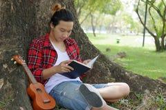Книга чтения молодого человека в парке с гавайской гитарой стоковые фото