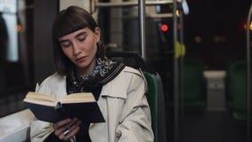 Книга чтения молодой женщины или пассажира сидя публично переход, steadicam сняла ( Предпосылка светов города акции видеоматериалы