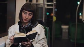 Книга чтения молодой женщины или пассажира сидя публично переход, steadicam сняла ( Предпосылка светов города сток-видео