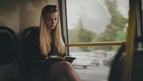 Книга чтения молодой женщины и смотреть вне окно пока управляющ в шине города сток-видео