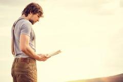 Книга чтения молодого человека внешняя с скандинавским озером на предпосылке стоковое изображение rf