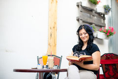 Книга чтения молодой женщины в кафе Стоковая Фотография RF
