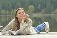 Книга чтения молодой женщины около озера стоковые фотографии rf