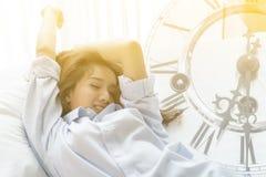 Книга чтения молодой женщины пока лежащ на кровати стоковое фото