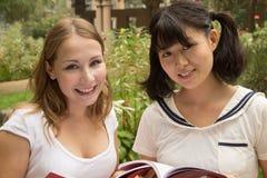Книга чтения молодых женщин в зеленом парке Стоковое Изображение RF