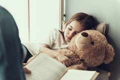 Книга чтения отца к спать маленькой девочке стоковое изображение
