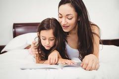 Книга чтения дочери с матерью на кровати Стоковая Фотография RF