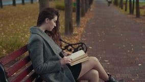 Книга чтения пальто спокойной молодой женщины брюнета нося сидя на стенде в парке акции видеоматериалы