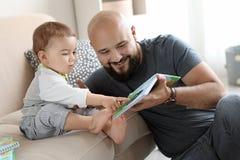 Книга чтения папы с его маленьким сыном стоковое фото rf