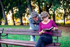 Книга чтения пар в парке Люди, образ жизни и relatio стоковое изображение rf