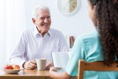 Книга чтения пенсионера и медсестры Стоковые Фотографии RF