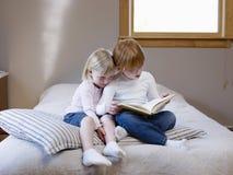 Книга чтения сестер на кровати Стоковые Изображения