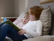 Книга чтения сестер на кровати Стоковое Фото