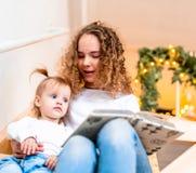 Книга чтения старшей сестры aloud к ее более молодой сестре на лестнице стоковое изображение rf