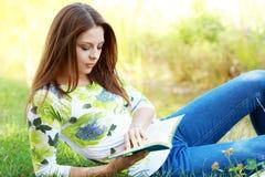 Книга чтения студента девушки в парке осени. Стоковые Изображения RF