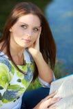Книга чтения студента девушки в парке осени. Стоковое фото RF