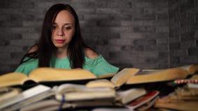 Книга чтения студента женщины буря на библиотеке с много книгами в университете Привоженная в уныние студентом книга чтения для акции видеоматериалы