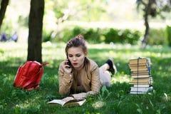 Книга чтения студента маленькой девочки лежа на траве в парке стоковые изображения