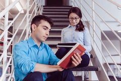 Книга чтения студентов совместно в библиотеке Стоковое фото RF