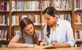 Книга чтения учителя и девушки в библиотеке Стоковая Фотография RF