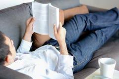 Книга чтения человека пока лежащ на кресле Стоковое Изображение
