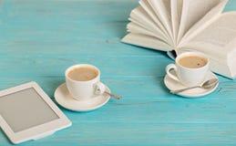 Книга, eBook и 2 белых чашки кофе на деревянном голубом backg Стоковое Изображение RF