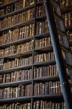 Книга Kells, книжные полки, длинная библиотека комнаты в коллеже троицы Стоковые Фотографии RF
