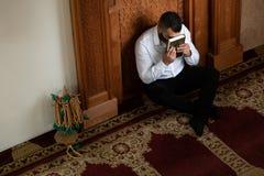 Книга Koran мусульманского человека целуя святая исламская стоковые изображения