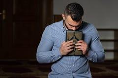 Книга Koran мусульманского человека целуя святая исламская стоковое фото rf