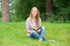 книга outdoors читая детенышей женщины Стоковые Фото